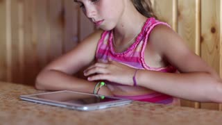 Girl sits at the table and uses tablet computer. Nice girl uses tablet pc. Female with tablet pc
