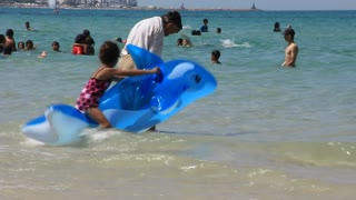Girl with blue inflatable dolphin in sea