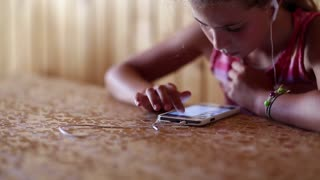 Girl with earphones looks web pages on his smartphone. Girl with earpieces and smartphone. Child with smartphone. Pretty girl sits at the table and uses smartphone