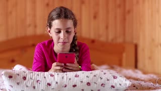 Girl with red smartphone lies on the bed. Nice girl lies on the bed and talks on mobile phone. Female with cell phone