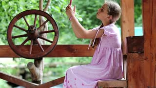 Girl with red smartphone sits near wooden wheel. Female makes photos on his smartphone. Young attractive girl holds in hands mobile phone