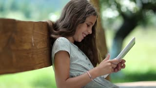 Girl with tablet computer. Nice girl playing the game on Tablet PC. Nice girl with Tablet-PC sits on the bench. True sincere emotions. Beautiful girl with tablet computer. She was captivated by game