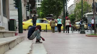 GREECE, ATHENS, JUNE 7, 2013: Beggar and people on the street in Athens, Greece