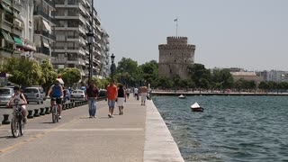 GREECE, THESSALONIKI, JUNE 10, 2013: White tower and people on the waterfront in Thessaloniki, Greece