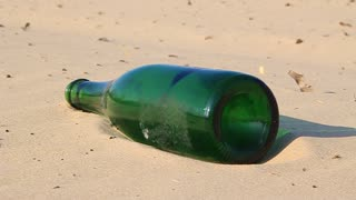 Green bottle on the sand