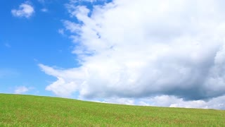 Green flank of hill and blue sky with clouds