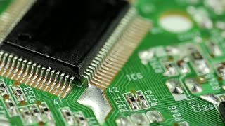 Green microcircuit chip with electronic components. Close-up of micro circuit, resistors and chips. Chips and resistors on green circuit board close up.Close up of electronic circuit board, macro lens