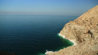 Green water and white salt deposits on yellow rocks. Rocky shore of Dead Sea in Hashemite Kingdom of Jordan