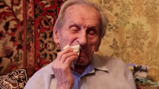 Grey-haired 93-year old man carefully wipes his lips after eating