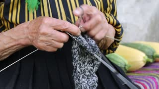 Hands of old woman who sits on the bench and knits wool socks. Old woman sits on bench near his house and knits sock. Ukrainian old woman is engaged in knitting. Female in kerchief knits woollen sock