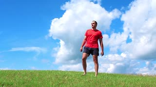 Healthy life-style. Man on red t-shirt on green grass
