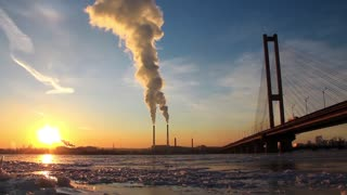 Heat electropower station with two smoking chimneys and big bridge over frozen river