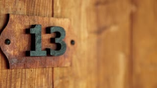 Hotel room number thirteen. Wooden door of room number 13. House doorplate number thirteen, bakers dozen, seventh Fibonacci number close-up. Triskaidekaphobia - superstitious fear of number thirteen