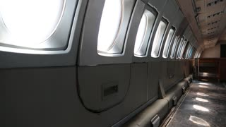 Inside the airplane. Empty interior of old airliner. Interior of aircraft without passenger seats