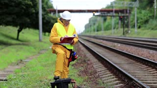 Inspector of railway traffic makes notes in his documents. Railway employee in yellow uniform on railway line. Railway worker in yellow uniform and white hard hat with documents in hands