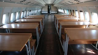 Interior of old airliner with desks. Inside the airplane. Interior of old airliner without passenger seats