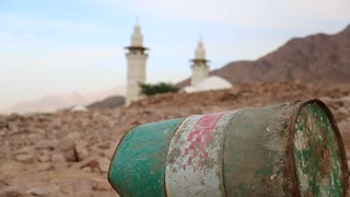 Iron barrel lies on the stony ground, mosque with two minarets on the background in defocus. Mosque and oil barrel. Old green rusty cask in mountain in Aqaba, Jordan. Empty barrel, lack of fuel