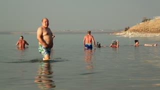 JORDAN, DEAD SEA, DECEMBER 8, 2016: People swim in Dead Sea. People relax in very salty water of Dead Sea, Hashemite Kingdom of Jordan
