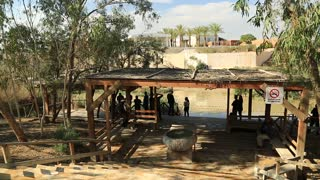 JORDAN, JORDAN RIVER, AL-MAGHTAS, DECEMBER 8, 2016: People near Jordan river in Al-Maghtas, historical place of baptism of Jesus Christ. View on Qasr El Yahud in Israel from Jordan