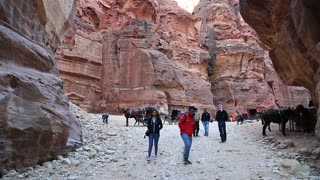 JORDAN, PETRA, DECEMBER 5, 2016: People in narrow passage, red gorge that leads to Petra, originally known to Nabataeans as Raqmu - historical and archaeological city in Hashemite Kingdom of Jordan