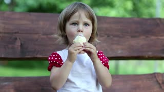Little cheery girl sits on the swing bench eats ice cream and licks her lips