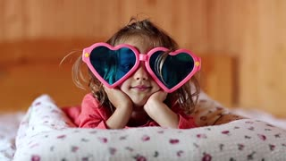 Little girl in big glasses in the shape of hearts lies on the bed. Funny little girl lies on the pillow and looks at the camera