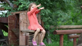 Little girl in red dress sits on a bench. Funny little girl sits on the chair with spring