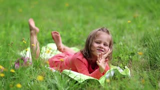 Little girl lies on the grass and waves arm. Funny little girl in glasses lies on the green grass and looks at the camera