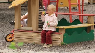 Little girl on children's playground with soap bubbles