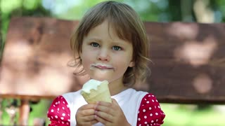 Little girl sits on the bench eats ice cream and licks her lips