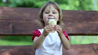 Little girl sits on the bench eats ice cream and licks his lips
