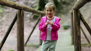Little girl stands on a wooden bridge and does dance moves. Funny little girl in pink jacket on the nature