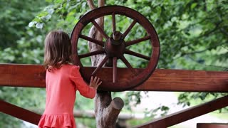 Little girls turn wooden wheel. Funny little girl in red dress turn wooden wheel