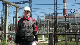 Maintenance staff with working drawings at nuclear power station. Worker in white helmet with engineering drawing near outdoor switchgear at atomic power station