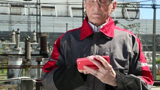 Maintenance worker with red smartphone at power station. Power engineering specialist with red smartphone at heat station. Worker in yellow hard hat at heat station. Factory worker with red smartphone