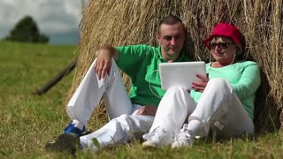 Man and woman sits near haystack and communicates via Tablet PC. Mother and son with tablet computer. Woman and man with Tablet-PC communicates through Skype. Male and female with electronic device