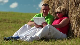 Man and woman with Tablet-PC sits near a haystack. Mother and son with tablet computer looks and flips through the photos on tablet computer