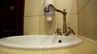 Man carefully washes hands with soap, turns on cold and hot water, bronze old bib and round white washbowl
