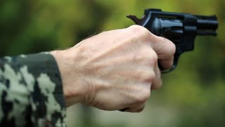 Man holds in hands black revolver. Retired officer at shooting range. Senior man shoots a pistol in forest. Man with black gun, close up