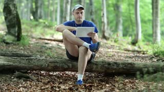 Man in blue t-shirt sits on a fallen tree in the forest and communicates via Tablet PC. Adult man sits on a fallen tree in the forest and uses tablet PC. Communication through skype