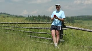 Man in blue t-shirt stands in the field and communicate via smartphone