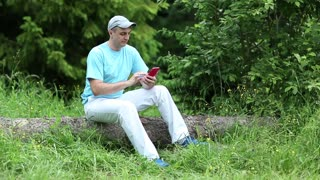 Man in blue t-shirt with a cell phone sits on a fallen tree in the forest. Adult man sits on a fallen tree in the forest and communicates via smartphone