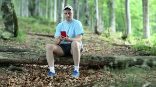 Man in blue t-shirt with red smartphone sits on a fallen tree in the forest. Man with smartphone. Sportsman with cell phone in the forest