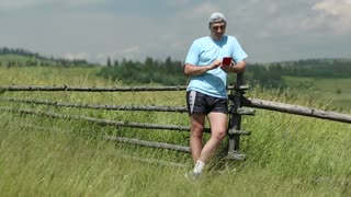 Man in blue t-shirt with smartphone with earphones stands in the field