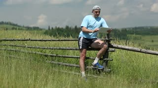 Man in blue t-shirt with tablet PC and earphones stands near old wooden fence in the field