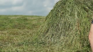 Man in dark blue t-shirt lying on a haystack. Physical and mental rest