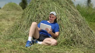Man in dark blue t-shirt with tablet computer lies on a haystack. Man uses tablet PC. Male with tablet computer. Sportsman with Tablet PC