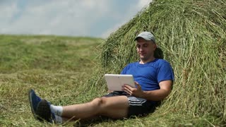 Man in dark blue t-shirt with tablet computer lying on a haystack. Man uses tablet PC