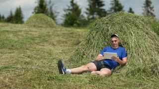 Man in dark blue t-shirt with tablet computer sits near a hayrick. Adult man sits on a green grass and uses tablet PC