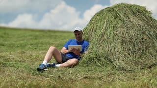 Man in dark blue t-shirt with tablet PC sits near a haystack